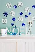 White and blue stylised ice flowers on wall above Christmas decorations on cabinet