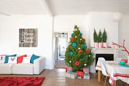 Christmas tree and presents next to fireplace in interior