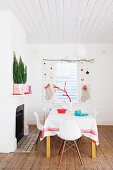 Dining table in front of festively decorated window and shutters