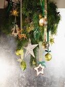 Tannenzweig mit Weihnachtsdeko vor silberfarbener Wand aufgehängt
