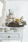 Geschenketurm im Kranz aus Weidezweigen auf Shabby Tisch und Weihnachtskugeln in offener Schublade