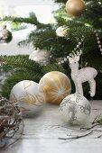 Weihnachtskugeln und Rentierfigur an Tannenzweigen gehängt