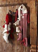 Babykleidung mit weihnachtlichen Motiven an Wandhakenleiste auf rustikaler Holzwand