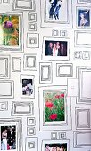 Souvenir photos arranged in picture frames of various sizes painted on interior wall