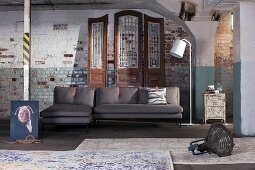 Absurdist arrangement of chaise sofa, standard lamp and rugs against old brick wall