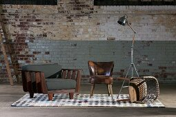 Armchairs, tipped over wooden chair and retro standard lamp against old brick wall