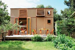Summer atmosphere in garden with terrace adjoining cubic prefab house