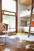 Bunk beds next to floor-to-ceiling window with view of garden and cowhide rug on floor in foreground