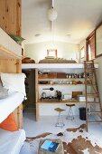 Multifunctional interior with cowhide rug on floor in front of improvised kitchen fittings below sleeping gallery