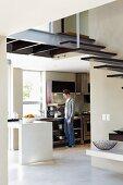 Offene Wohnküche; im Vordergrund Stahltreppe mit holzbelegten Stufen