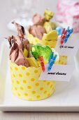 Paper baking cases of sweets decorated with mottoes & miniature clothes pegs