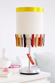 Lampshade decorated with clothes pegs
