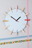 Wall clock made from cardboard and clothes pegs