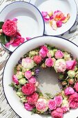 Wreath of pink roses in enamel bowl and petals on plates