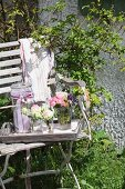 Delicate posies of roses in drinking glasses and preserving jar with ribbon on tray on old garden chair