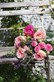 Bouquet of plump roses on old garden chair
