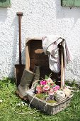 Rustic still-life arrangement of rose bouquet and balls of twine in wicker basket against house facade