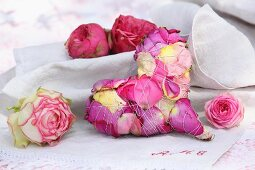 Decorative heart made from bound rose petals and rose blooms on monogrammed linen cloth