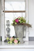 Arrangement of roses with stone and glass vases in front of old window casement