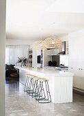 Barhocker mit Metallgestell an weisser, freistehender Küchentheke unter Korbhängeleuchten in Designerwohnung