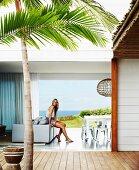 Innenhof mit Palme vor offenem Wohnraum mit Frau und Blick durch offenes, raumhohes Fenster auf das Meer