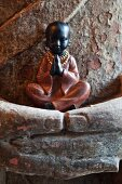 Small figurine of praying boy held in folded hands of larger statue