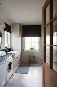 View into utility room with washing machine, dark Roman blinds and tiles in pale, natural shades