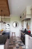 Retro-style, combination gas-electric cooker and sink unit with charcoal stone counter in county-house kitchen with marble floor tiles in natural colours