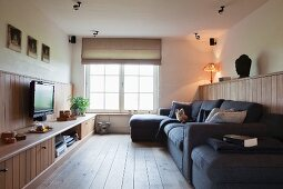 Living room with TV, sofa combination and media cabinet integrated into wooden dado