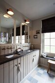 Country-house washstand counter with black counter, retro tap fittings and fitted mirrored cabinets