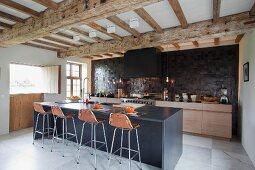 Weiträumige, moderne Küche mit Frühstückstheke unter der renovierten Holzbalkendecke in ehemaligem Stall
