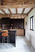 Moderne Designerküche mit Barhocker an Frühstückstheke unter der renovierten Holzbalkendecke in ehemaligem Stall