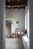 Blick durch offene Tür auf Holzstuhl neben altem, offenem Ziegelkamin