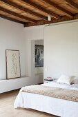 Doppelbett mit einfachem Holzhocker als Nachttisch und Aktzeichnung neben türlosem Durchgang zum angrenzenden Raum