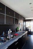 Moderne Küchenzeile mit schwarzen Fronten in offenem Küchenbereich mit Einbaustrahlern in abgehängter Decke