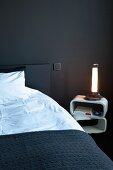 Bett mit schwarzer Tagesdecke neben Retro Nachttisch und leuchtender Tischlampe in schwarz getöntem Schlafzimmer