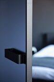 Blick durch halboffene Tür auf Bett im Schlafzimmer
