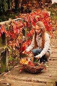 Junges Mädchen beim Herbstlaub sammeln