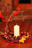 Weisse Kerze in Kranzmitte aus Kastanien und Herbstblättern vor Vase mit Hagebuttenzweigen auf Tisch