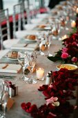 Wedding table decorated with tealight and red roses