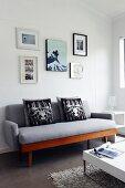 Fotogalerie über grauem Sofa im Retrostil, weisser Couchtisch mit verchromten Füssen auf Hochflorteppich