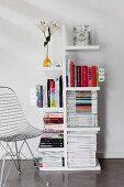 Bücher und Zeitschriften auf Designerregal mit auskragenden Fächern, seitlich ein Drahtgitterstuhl von Eames