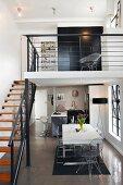 Blick auf Essplatz und offene Küche, seitlich eine Treppe zum Galeriegeschoss