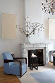Art Deco interior with open fireplace, elegant armchair with pale blue leather upholstery and dark wood side table