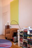 Several stacks of books on floor next to light brown leather armchair below pale yellow monochrome artwork on wall