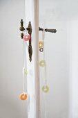 Sweeties tied on decorative ribbons on pair of vintage door handles on door with glass panel