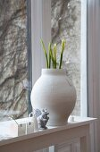 Flower buds in white clay pot on windowsill and view of climber-covered exterior wall