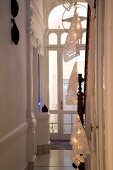 String of fairy lights with paper shades in grand stairwell with arched glass door
