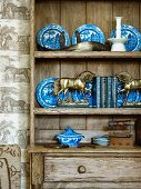 Miniature horse statues in brass and blue and white crockery on dresser shelving