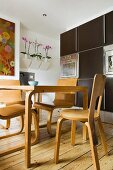 Dining area with Scandinavian-style wooden chairs and table in front of dark, modern, fitted kitchen cabinets